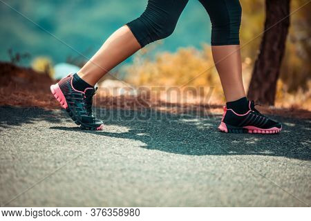 Photo of a Sportive Woman Jogging Outdoors. Body Part. On the Walk. Weight Lost. Active Healthy Lifestyle.