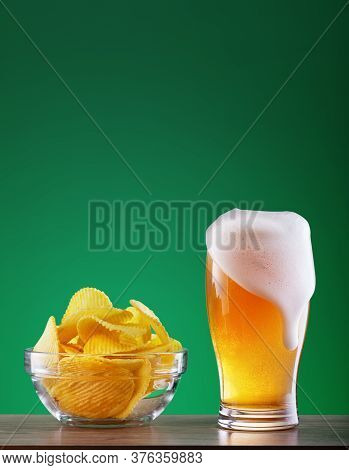Glass Of Light Beer With Leaky Foam And Dish Of Chips