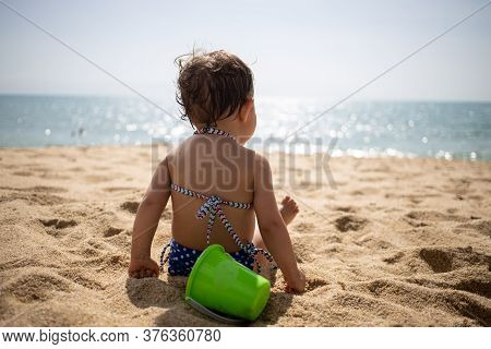 Philosophy Philosophy Of Children. Little Cute Toddler Tanned Caucasian Girl In A Blue Bathing Suit