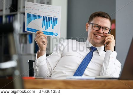 Businessman Holds Report And Speaks On Phone. Happy Man Talks On Phone About Successful Financial Re