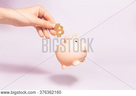 Bitcoin Holding Concept. Piggy Bank For Bitcoins. Cryptocurrency Saving Symbol. A Woman Puts Bitcoin