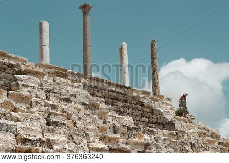 Tourist Woman Goes Down the Stairs  From the Top of Ruins Of Tyre. Enjoying Beauty and Majesty of Necropolis. Travel to Lebanon. World Heritage.