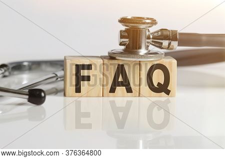 Faq The Word On Wooden Cubes, Cubes Stand On A Reflective White Surface, On Cubes - A Stethoscope. M