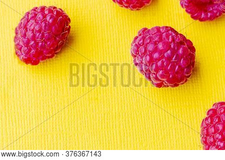 Yellow Background. On It Is A Red Berry Raspberry. Close-up.