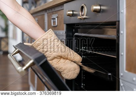 Cropped View Of Woman Hand In Kitchen Glove Mitt Pull Out Tray From Built In Oven With Open Door. Co
