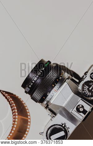Geometric Flat Lay Set: Vintage Camera On Light Backgrounds With 35 Mm Filmstrip. Top View.