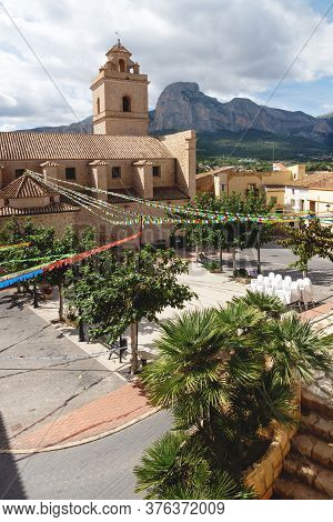 Main Square With Colorful Flags At The Church Of Polop De Marina With Rocky Mountainrange, Costa Bla