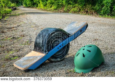 One-wheeled electric skateboard with a helmet on wet and muddy Steamboat Trail converted from abandoned railroad running along Missouri River between Bronville and Nebraska City, NE.