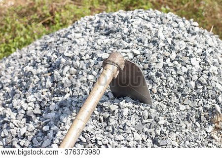 Pile Of Construction Gravel Or Stone With Hoe At Construction Site In The Heat Of The Sun.