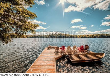 People With Muskoka Chairs Sitting On A Wood Dock Facing A Calm Lake. Across The Water Is A White Co