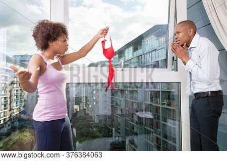 Angry young woman holding bra in front of guilty man at home
