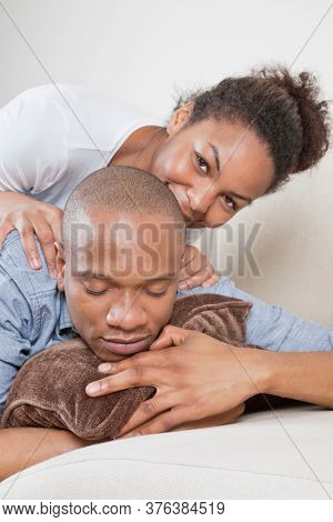 Portrait of happy young woman with partner sleeping on sofa