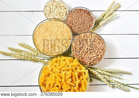 Carbohydrates. Pasta, Rice,oats, Peal Barley And Wheat.crouts In Bowls On White Wooden Background. F