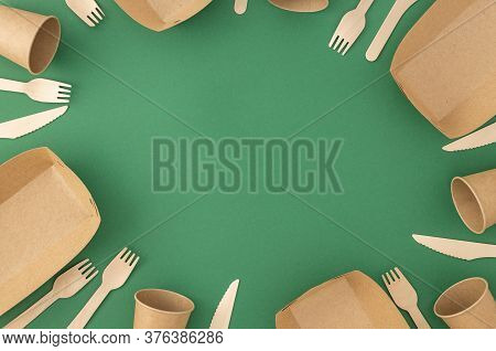 Frame Of Disposable Paper Cups And Plate With Wooden Forks And Knives On Green Background Pattern Ze