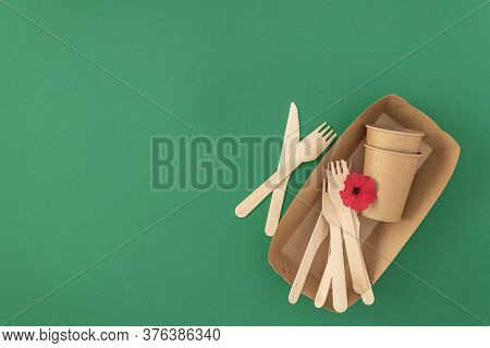 Frame Of Disposable Paper Cups And Plate With Wooden Forks And Knives On Green Background With Copy