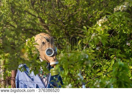 Mannequin With A Gas Mask In The Green Foliage Of Trees, Symbolizing The Problem Of Air Pollution, T