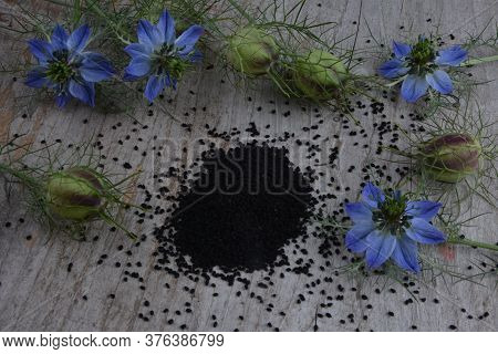 Black Cumin (nigella Sativa Or Kalonji) Seeds In Heart-shaped Bowl On Wooden Background
