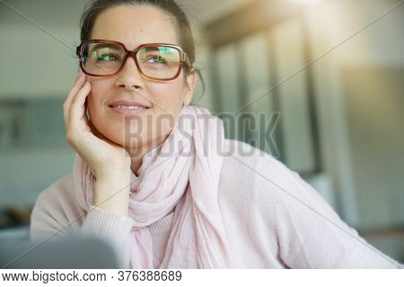Smiling dark-haired woman with eyeglasses working on laptop