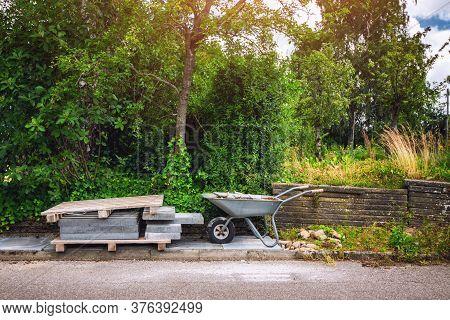 Wheelbarrow With Tiles On A Street Behind A Green Garden