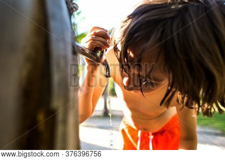 Tired Of Heat, The Child Quenches Thirst From A Tap In The Courtyard Of The House. The Boy Drinks Wa
