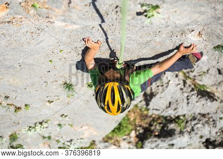 The Child Is Climbing On A Natural Terrain. A Boy In Helmet Climbs A Rock On A Background Of Mountai