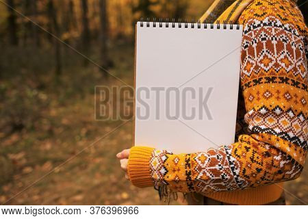 Autumn Mock Up. Autumn To-do List.back To School.girl In A Brown Sweater Holds A Blank Notebook On A