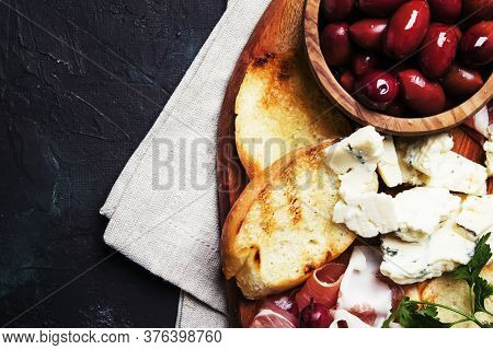 Snacks Or Antipasti, Crostini, Prosciutto, Blue Cheese And Olives, Black Background, Top View