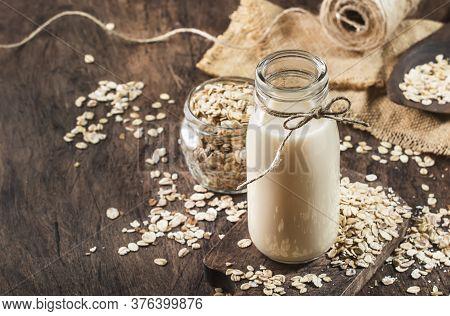 Vegan Oat Flakes Milk, Non Dairy Alternative Milk In Glass, Wooden Rustic Table, Copy Space
