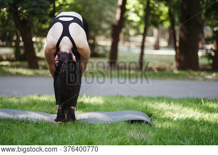 Outdoor Yoga. Young Woman Doing Physical Exercises On Fitness Mat. Leisure, Self Development, Mental