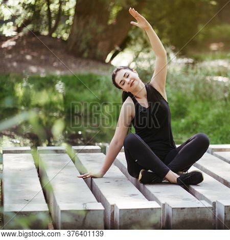 Outdoor Yoga. Young Woman Meditating In The Park Near Running Water. Nature, Open Air Leisure Activi