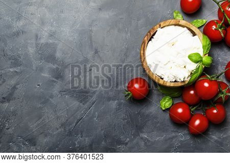Soft Ricotta Cheese In A Wooden Bowl With Green Basil And Cherry Tomatoes, Gray Stone Background, To