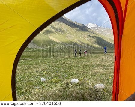 View From The Tent: Climbers With Backpacks And Trekking Poles Walk Through Alpine Meadows. Aerial V