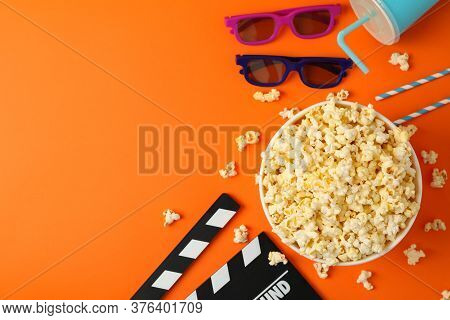 Composition With Bucket Of Popcorn On Orange Background. Food For Watching Cinema