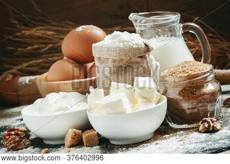 Baking Ingredients: Milk, Butter, Flour, Sugar, Eggs And Rolling Pin On A Floured Table In A Rustic