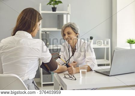 Senior Doctor Checking Patient Blood Pressure At Hospital. Young Woman Consulting Cardiologist At Cl