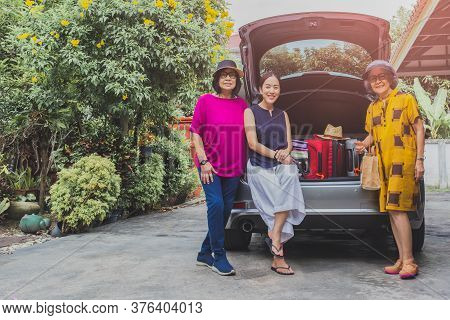 Two Senior Woman And One Adult Woman Sitting In Back Of The Car With Suitcases On Car Trip.