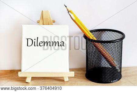 Dilemma Concept Written On A Small Blackboard On Easel