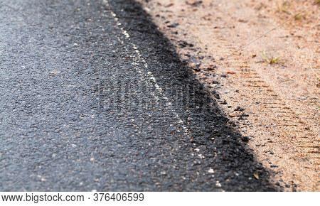 New Asphalt Road Edge And Sandy Roadside. Abstract Transportation Background Photo With Selective So
