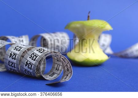 Stub Of A Green Apple With A Centimeter Tape On A Blue Background
