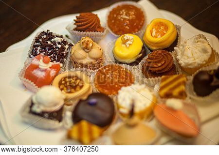 Different Sort Of Beautiful Pastry, Small Colorful Sweet Cakes On A Plate. High Quality Photo