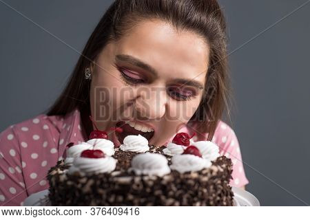 Portrait Of A Girl Biting A Cake. Studio Photo On A Gray Background