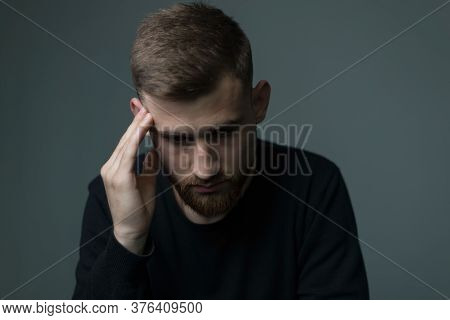 Suffering From Headache A Young Bearded Guy Of About Twenty Five, In Black, Presses His Hand To His