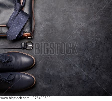Set of men's classic clothes as tie, belt, shoes and bag on stone background with copy space. Top view flat lay