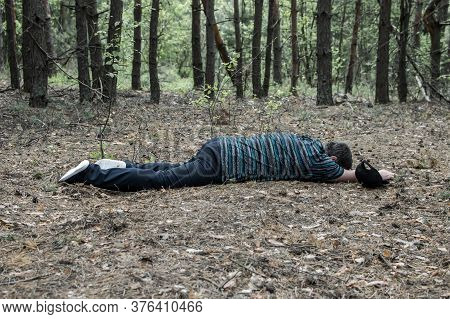 Murder In The Woods. The Body Of A Man In A Blue T-shirt And Trousers Lies On The Ground Among The T