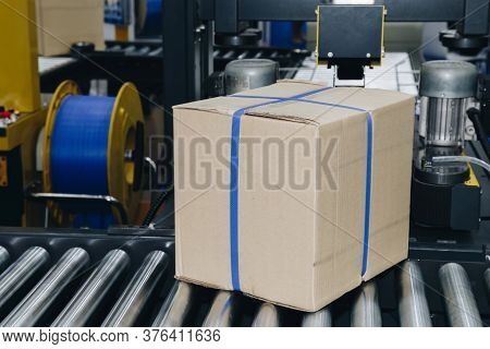 Cardboard Box Of Product Packaging Is Moving On Conveyor Belt Of Automatic Packing Machine In The Ma