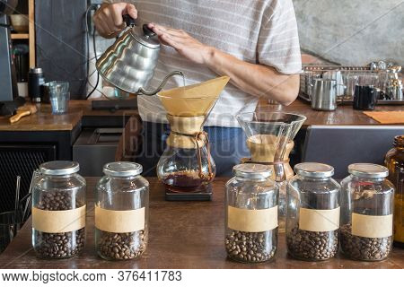 Barista Holding Drip Pot And Pouring Water Onto Ground Coffee Beans In The Paper Filter For Brewing