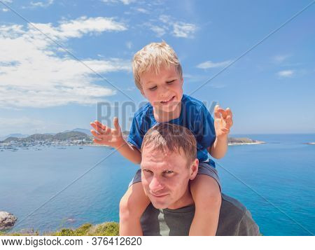Front Boy Son Laugh Sitting On Fathers Shoulders. No Photoshop Sun On Skin. Sea, Clouds, Island Back