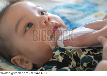Asian Mother Is Wiping Her Baby's Face After Infant Baby Boy Vomiting. People And Family Lifestyle C
