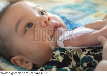 Asian Mother Is Wiping Her Baby's Face After Infant Baby Boy Vomiting With Soft Sunbeam. People And