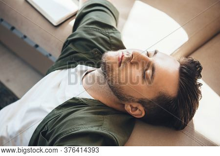 Tired Caucasian Man With Bristle Relaxing On A The Sofa After Reading A Book At Home